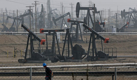 A person walks past pump jacks operating at the Kern River Oil Field in Bakersfield, California, on January 16, 2015. SOURCE: AP/Jae C. Hong